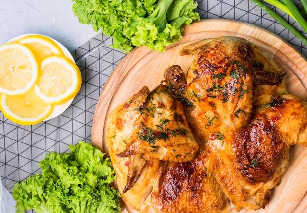 레몬 조각으로 커팅 보드에 구운 전체 치킨 상위 뷰 프리미엄 사진