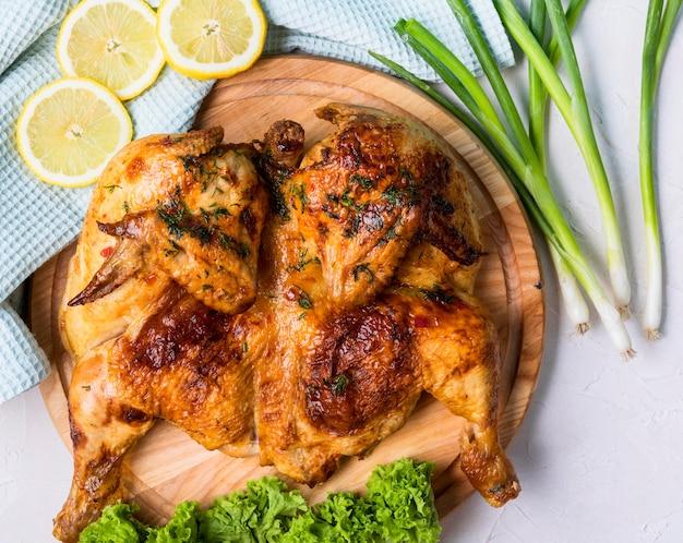 레몬 조각으로 구운 전체 치킨 상위 뷰 프리미엄 사진