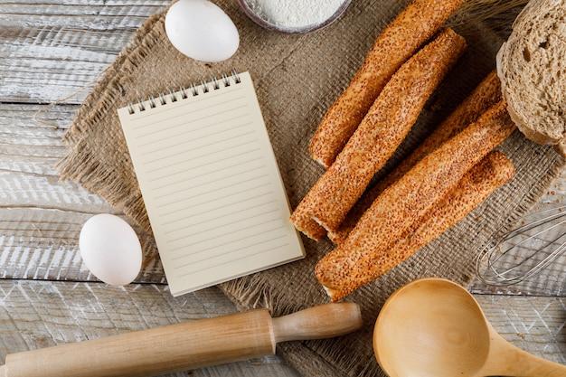 メモ帳、卵、袋の布や木の表面に麺棒でトップビューベーカリー。横型 無料写真
