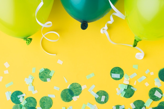 Top view of balloons and confetti frame on yellow background Free Photo