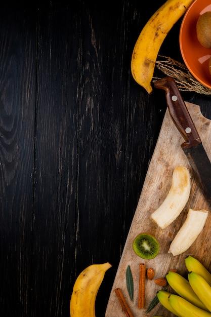 Vista superiore della frutta della banana con la mandorla, i bastoncini di cannella e il vecchio coltello da cucina su un tagliere di legno sul nero con lo spazio della copia Foto Gratuite
