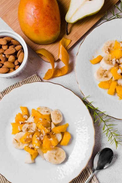 Top view of banana and mango on plates Free Photo