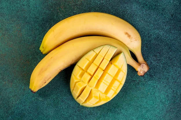 Top view bananas with chopped mangoes on a green table Free Photo