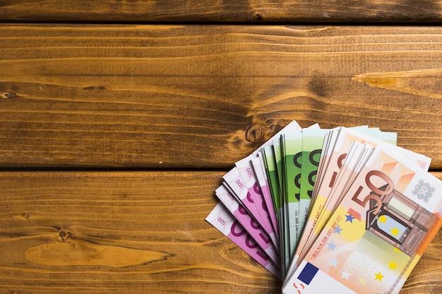 Вид сверху банкноты на деревянный стол Premium Фотографии