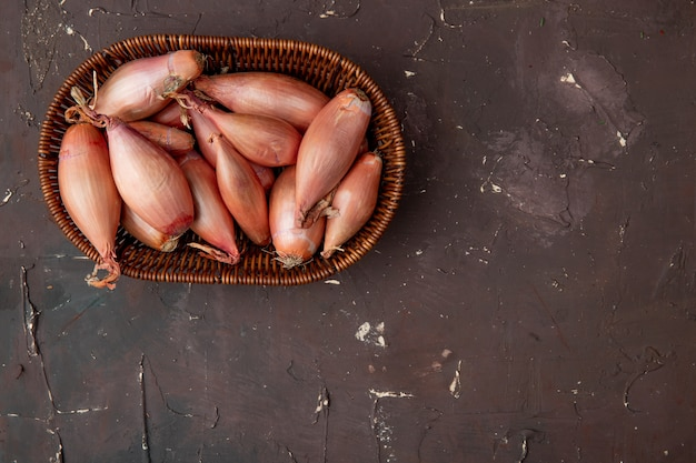 Top view of basket of shallots on left side and maroon background with copy space Free Photo