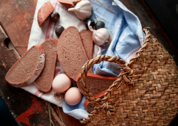Top view basket with bread slices eggs, plum and garlics around on a wooden table. Free Photo