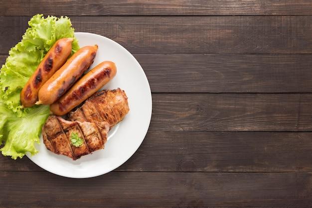 Bbq вид сверху гриль мясо, колбасы и овощи на блюдо на деревянных фоне. скопируйте место для вашего текста Premium Фотографии