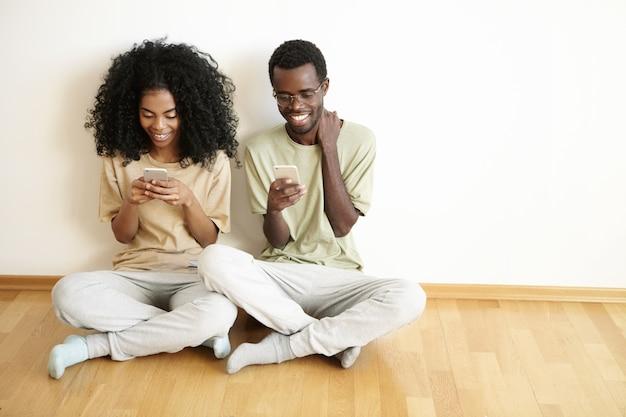 Vista dall'alto di bella giovane donna con acconciatura afro controllando newsfeed tramite i social network Foto Gratuite