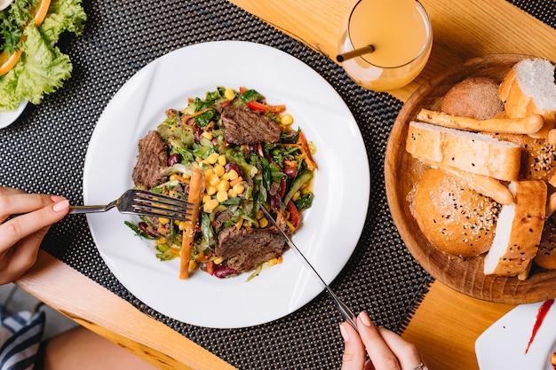 Вид сверху салат из говядины на гриле с помидорами, кукурузой, огурцом, салатом и хлебной палочкой на тарелке Бесплатные Фотографии