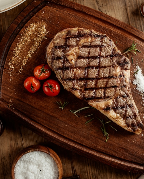 Top view of beef steak with salt herbs and cherry tomato served on board Free Photo