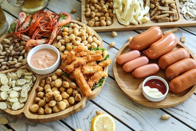 Вид сверху пивные закуски колбаски с жареным горохом фисташки гренки с креветками с сыром и соусами на подставках Бесплатные Фотографии