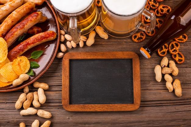 Birra vista dall'alto con cibo sul tavolo di legno Foto Gratuite