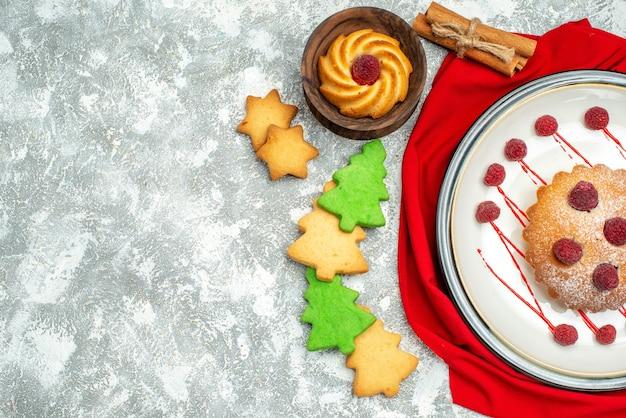 회색 표면 복사 공간에 흰색 타원형 접시 빨간 목도리 Cinamon 쿠키에 상위 뷰 베리 케이크 무료 사진