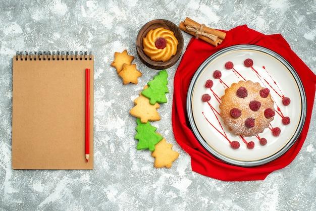 Torta di bacche di vista superiore sul piatto ovale bianco biscotti rossi della matita del taccuino dello scialle rosso sulla superficie grigia Foto Gratuite
