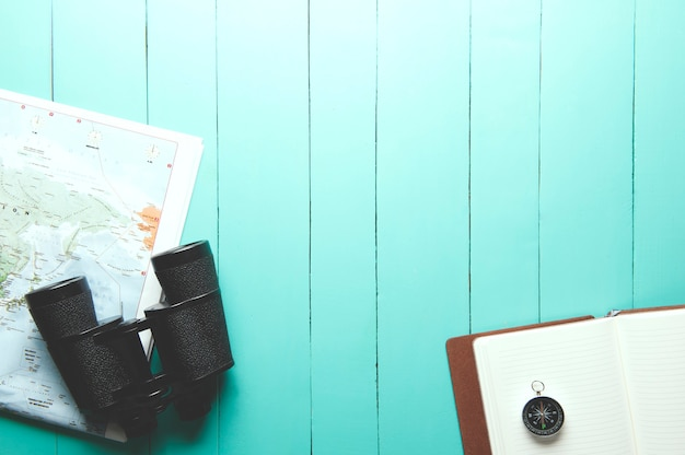 Top view of binocular, world map, compass and notebook on green wood background Premium Photo