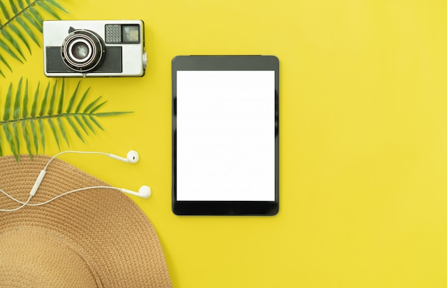 Top view of black digital tablet and hat with camera on yellow color background. summer holiday and travel concept. Premium Photo