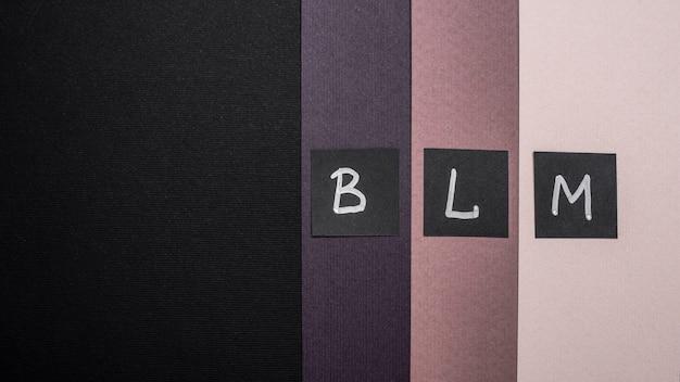 Vista dall'alto delle carte di materia viva nera con lettere su carta multicolore e spazio di copia Foto Gratuite
