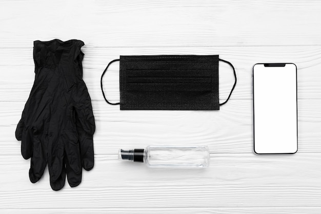 Top view black medical mask, gloves and blank phone Free Photo