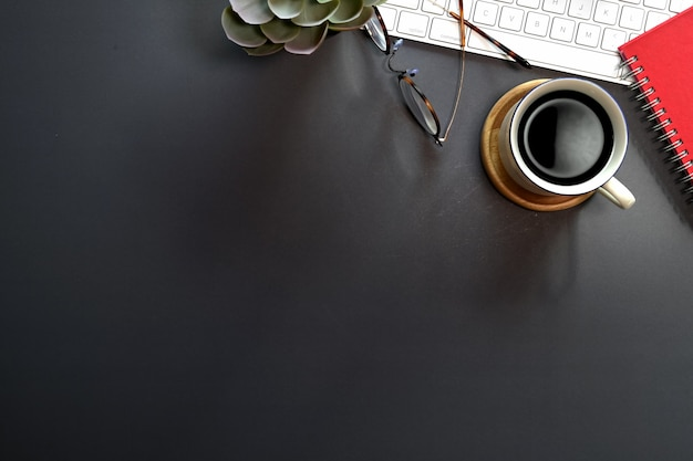Top view of black office desk with keyboard computer, office supplies and copy space Premium Photo