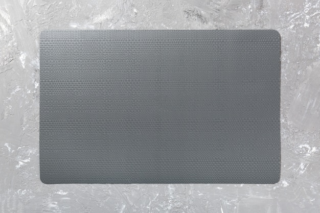 Top view of black place mat for a dish. cement background Premium Photo