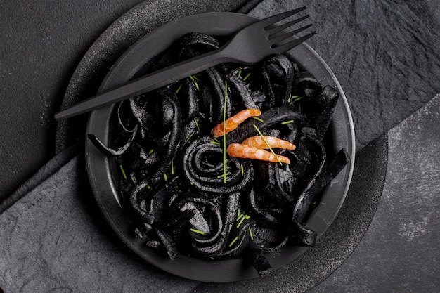 Top view black shrimp pasta with fork Free Photo