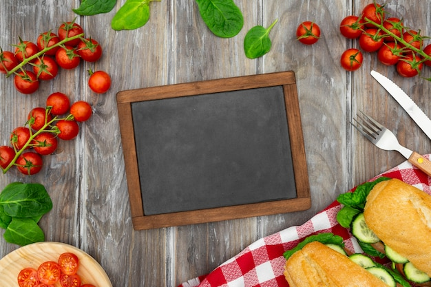 Top view of blackboard with tomatoes and sandwiches Premium Photo