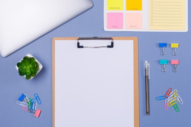 Top view of blank list on clipboard, to do list for the week, pen, stationery and laptop on light purple background, flat lay.  copy space. free space. schedule. timetable. Premium Photo