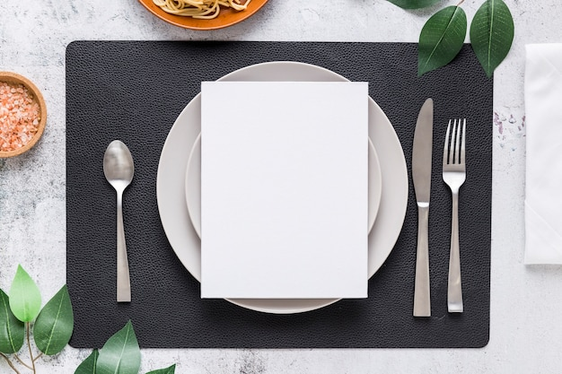 Top view of blank menu paper on plate with cutlery and leaves Free Photo