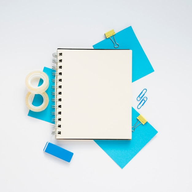 Top view of blank notebook over blue supplies Free Photo