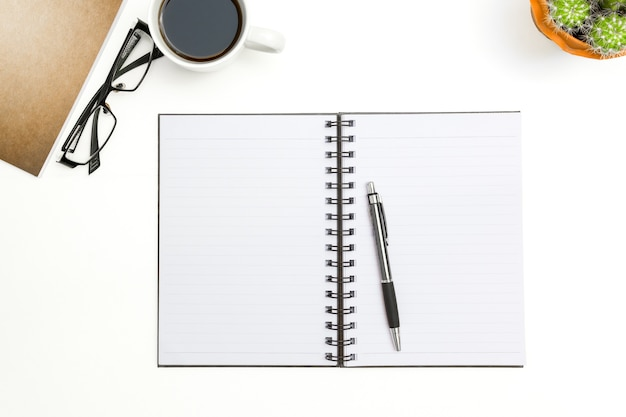 Top view blank notebook, pen and glasses on white desk background Premium Photo