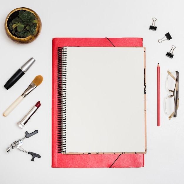 Top view of blank notebook with cosmetic products; paper clips; pencil; eyeglass over white desk Free Photo