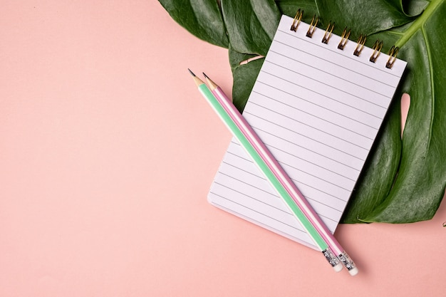 Top view of blank notebook with pen and monstera lief on pink pastel background with copy space Premium Photo