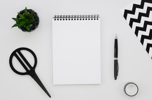 Top view of blank notebook with scissors and plant Free Photo