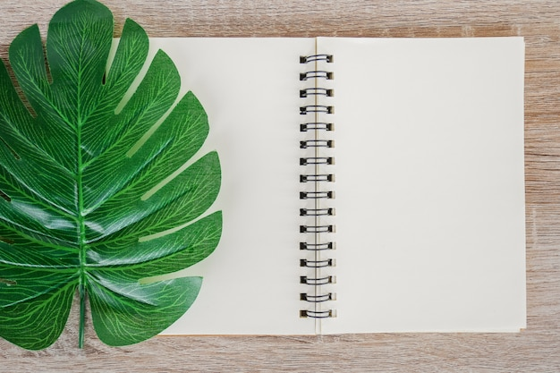 Top view of blank open notebook on wooden desk background with green tropical monstera leaves. Premium Photo