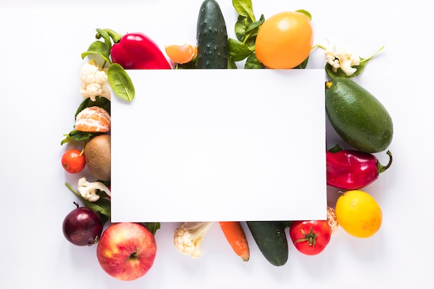 Top view of blank paper over fresh vegetables and fruits on white background Free Photo