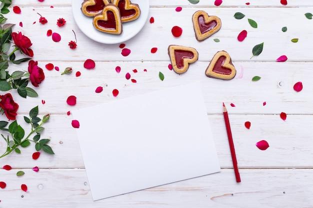 Vista dall'alto di un foglio di carta bianco su un tavolo di legno con biscotti e rose su di esso Foto Gratuite