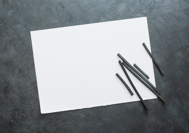 Top view of blank white sheet and natural hardwood charcoal stick Free Photo