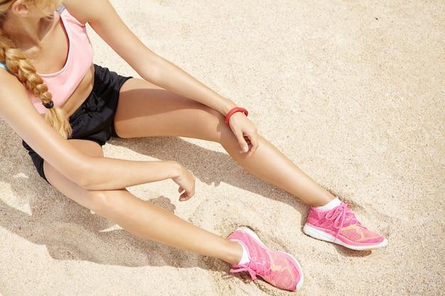 Vista dall'alto della ragazza bionda atleta caucasica con lunga treccia seduta sulla spiaggia sabbiosa che riposa le braccia sulle ginocchia, rilassante dopo una lunga corsa in riva al mare in giornata di sole, preparandosi per la maratona. Foto Gratuite