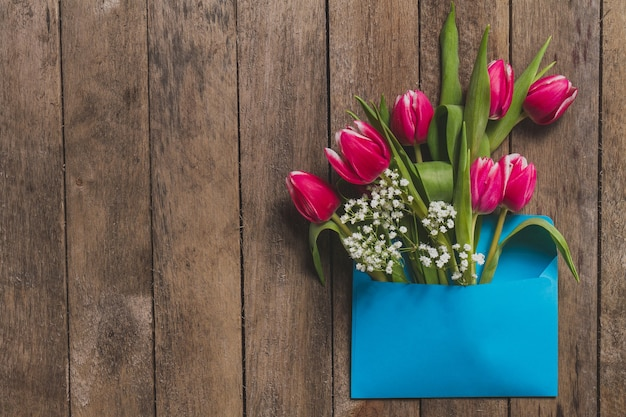 Top view of blue envelope with flowers on wooden table Free Photo