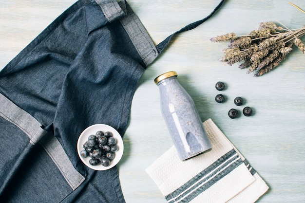 Top view blue smoothie and apron Free Photo