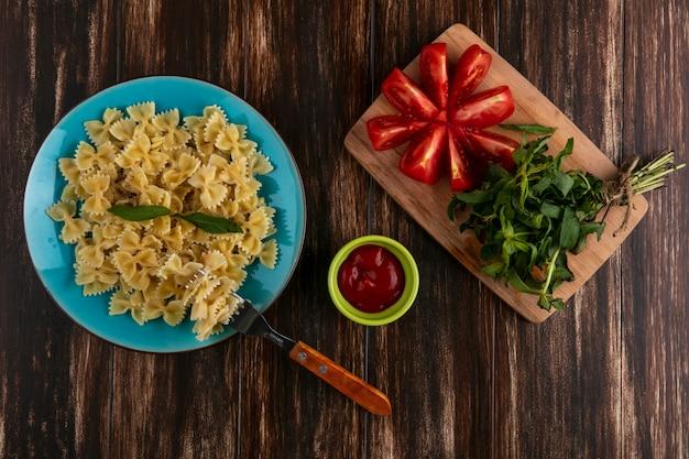 Vista dall'alto di pasta bollita su un piatto blu con una forchetta pomodori e un mazzetto di menta su un tagliere con ketchup su una superficie di legno Foto Gratuite