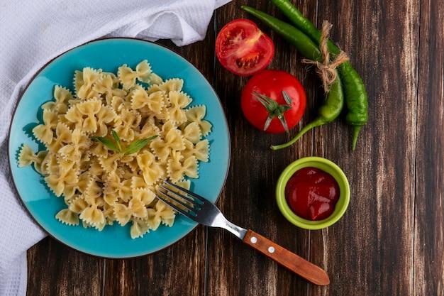 Vista dall'alto di pasta bollita su un piatto blu con una forchetta pomodori ketchup e peperoncino su una superficie di legno Foto Gratuite