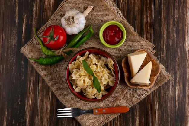 Vista dall'alto di pasta bollita in una ciotola con una forchetta pomodori peperoncino aglio e formaggio su un tovagliolo beige Foto Gratuite