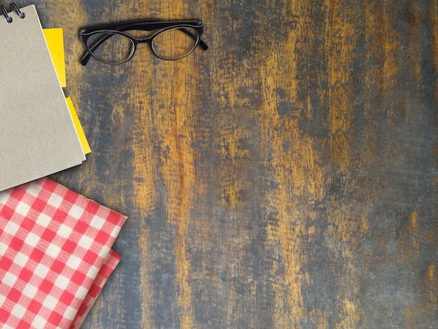 Top view of book and eyeglasses and plaid on wooden of brown, mock up Premium Photo