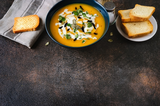 Top view of border made of traditional pumpkin soup and bread on dark vintage wood Premium Photo