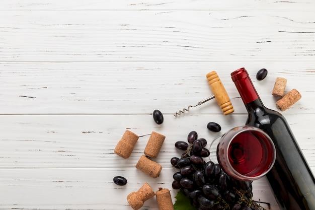 Вид сверху бутылка вина с бокалом и гроздью винограда Premium Фотографии