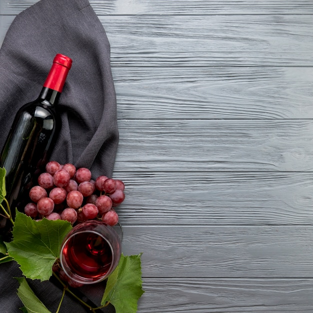 Top view bottle of wine with glass and bunch of grapes Free Photo