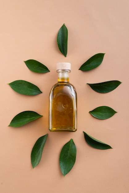 Top view bottles filled with oil surrounded by leaves Free Photo