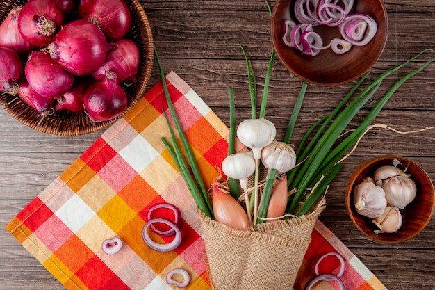 Top view of bouquet of vegetables as green onion garlic shallot on plaid cloth on wooden background Free Photo