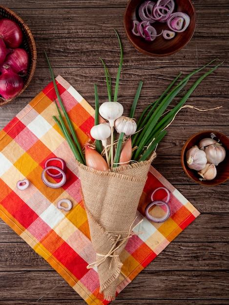 Top view of bouquet of vegetables as onion shallot and garlic on cloth on wooden background Free Photo